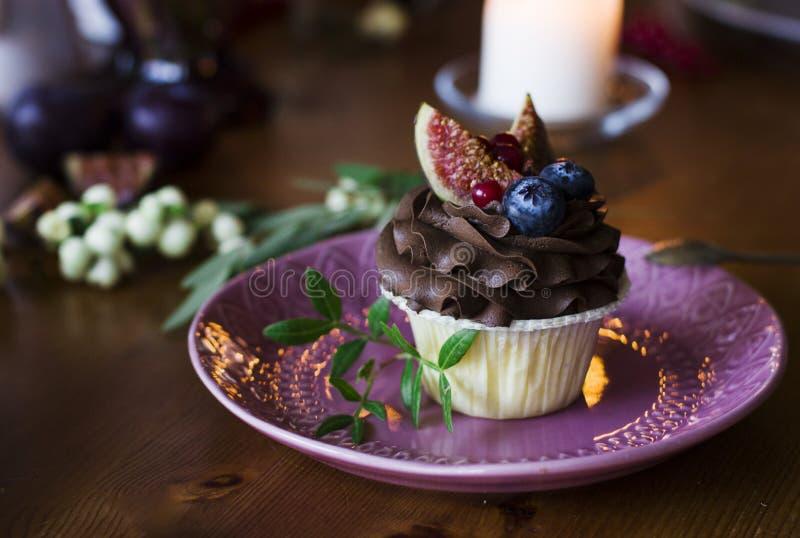 Σοκολάτα cupcake με τα σύκα και τα μούρα στον εορταστικό πίνακα στοκ φωτογραφία με δικαίωμα ελεύθερης χρήσης