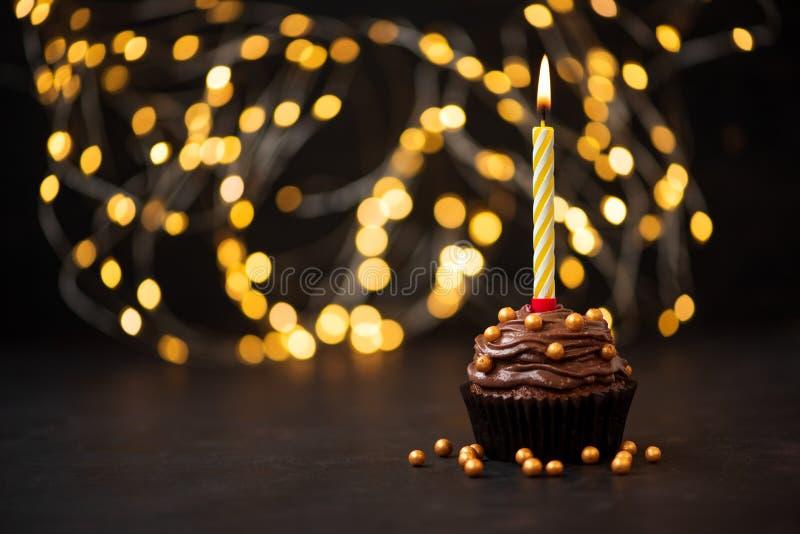 Σοκολάτα cupcake με τις χρυσές καραμέλες και το καίγοντας κερί στο σκοτεινό ξύλινο υπόβαθρο ενάντια στα θολωμένα φω'τα r στοκ εικόνα με δικαίωμα ελεύθερης χρήσης