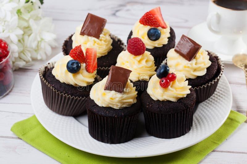 Σοκολάτα cupcakes με τις άσπρες φράουλες βακκινίων κρέμας στοκ φωτογραφία με δικαίωμα ελεύθερης χρήσης