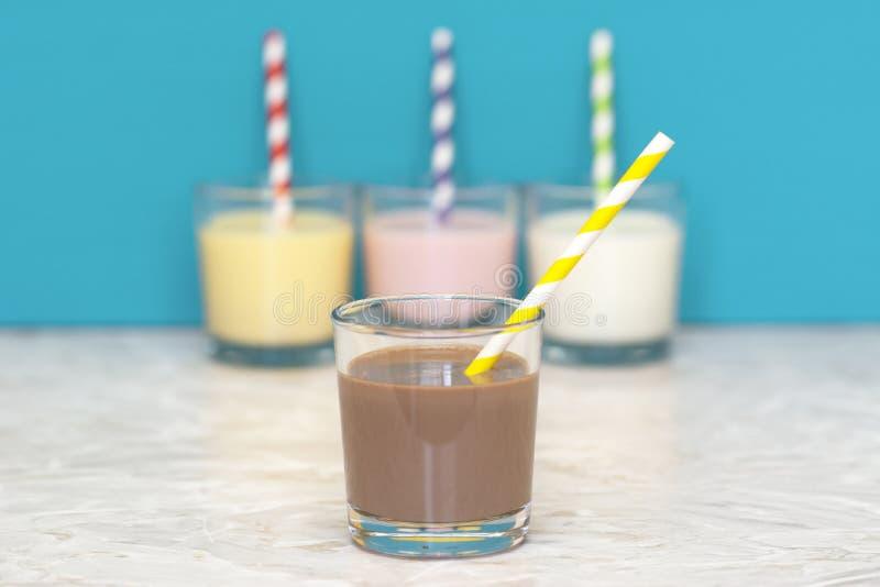 Σοκολάτα milkshake μπροστά από μια σειρά αρωματικός milkshakes στοκ εικόνα με δικαίωμα ελεύθερης χρήσης