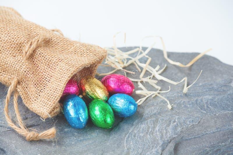 Σοκολάτες αυγών Πάσχας που προέρχονται από μια μικρή τσάντα γιούτας στοκ φωτογραφία