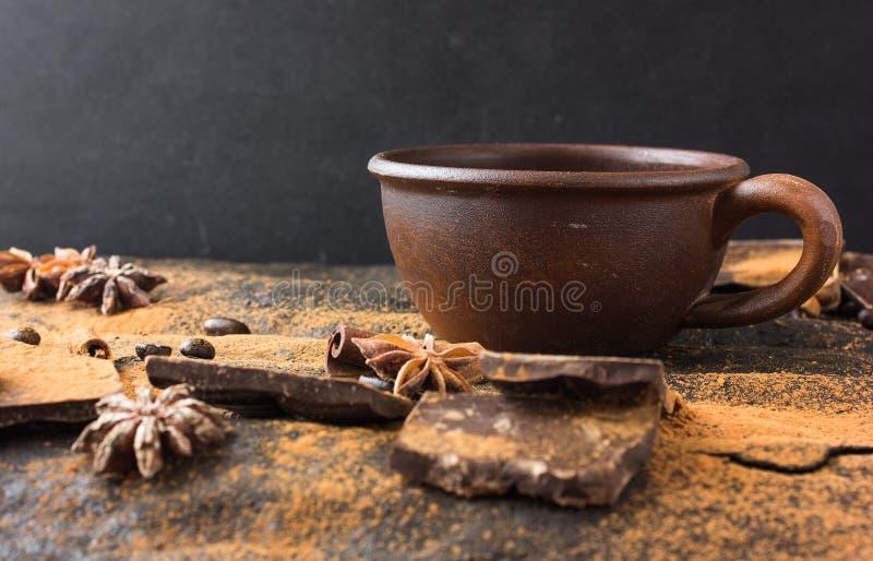Σοκολάτα, φασόλια καφέ, βαρελοειδή Καρυκεύματα, κακάο σε ένα υπόβαθρο θέματος grunge Μυστικό φως στοκ εικόνα με δικαίωμα ελεύθερης χρήσης