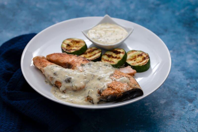 Σολομός με σάλτσα και ψητά λαχανικά σε λευκό πιάτο στοκ εικόνα με δικαίωμα ελεύθερης χρήσης