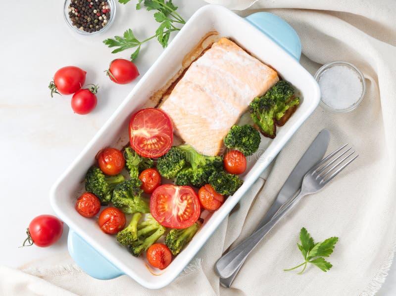 Σολομός ψαριών που ψήνεται στο φούρνο με τα λαχανικά - μπρόκολο, ντομάτες Υγιή τρόφιμα διατροφής, άσπρο μαρμάρινο σκηνικό, τοπ άπ στοκ εικόνα με δικαίωμα ελεύθερης χρήσης