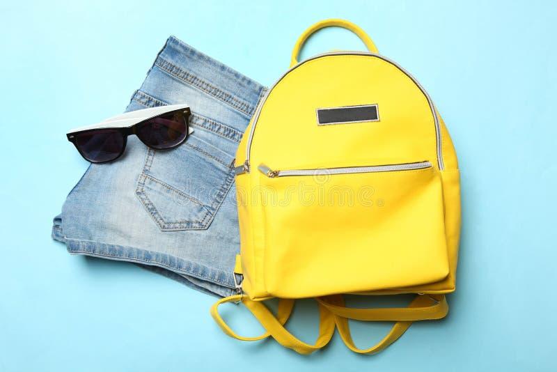 Σορτς, μοντέρνα κίτρινα σακίδιο πλάτης και γυαλιά ηλίου στοκ εικόνες