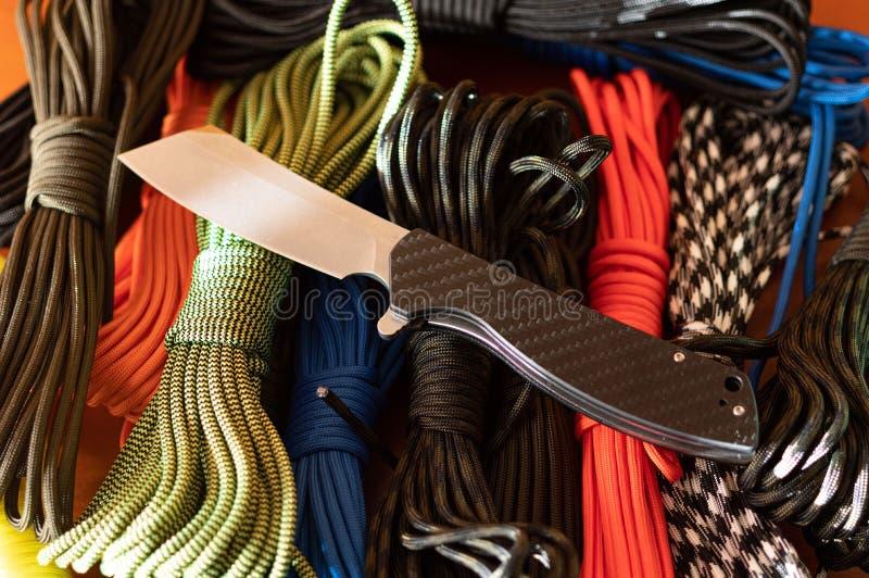 Σουγιά και πολύχρωμα σχοινιά Πτυσσόμενο μαχαίρι και αλεξίπτωτο στοκ φωτογραφίες