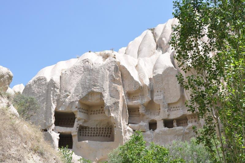 Σοφίτες Pigoen που χαράζονται σε Rockface - κόκκινο αυξήθηκε κοιλάδα, Goreme, Cappadocia, Τουρκία στοκ εικόνα