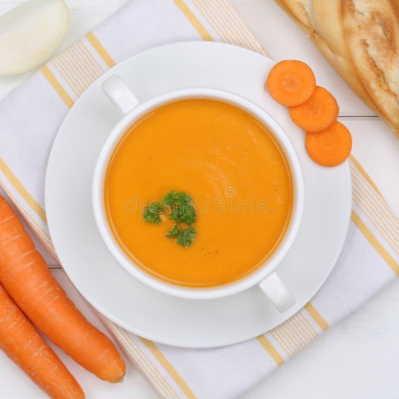 Σούπα καρότων με τα φρέσκα καρότα στην υγιή κατανάλωση κύπελλων άνωθεν στοκ φωτογραφία