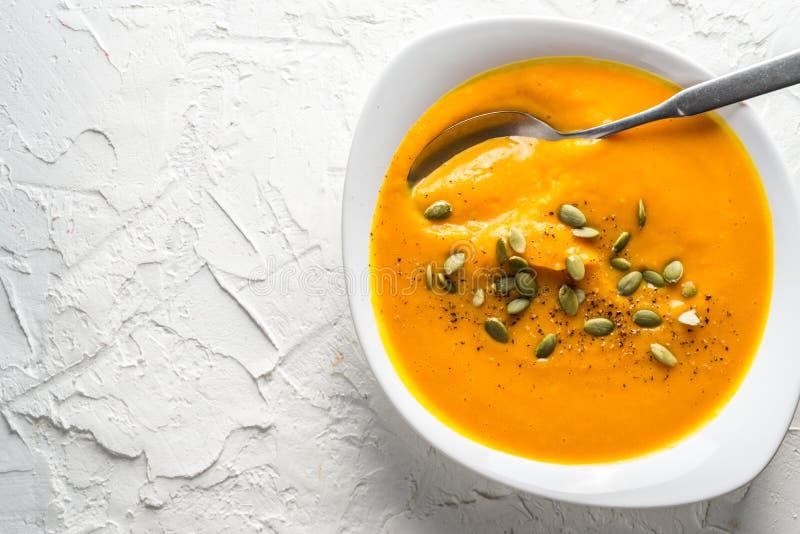 Σούπα κολοκύθας με τους σπόρους και ένα κουτάλι σε ένα πιάτο στοκ εικόνες