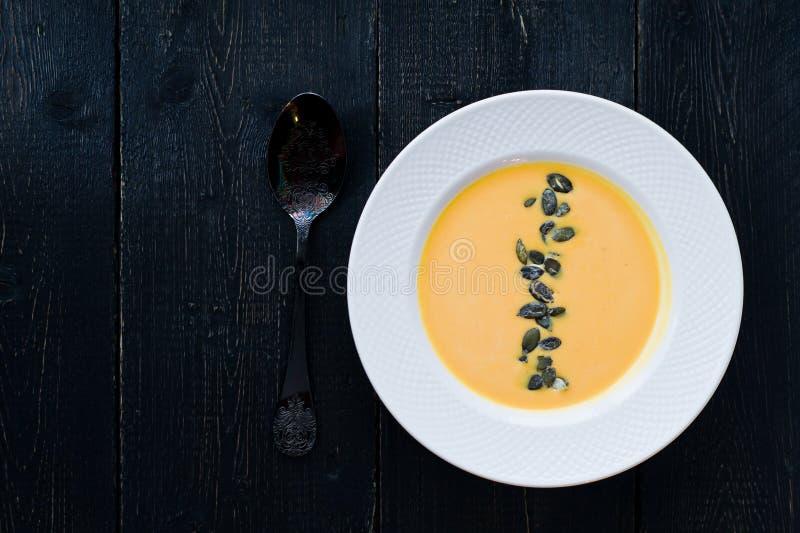 Σούπα κολοκύθας με τους σπόρους σε ένα άσπρο πιάτο σε ένα μαύρο υπόβαθρο στοκ εικόνες με δικαίωμα ελεύθερης χρήσης