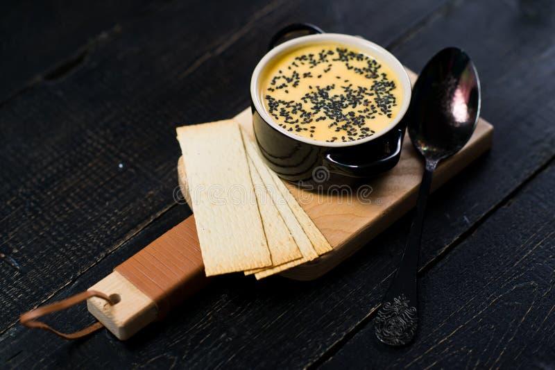 Σούπα κολοκύθας με το μαύρες σουσάμι και τις κροτίδες στοκ εικόνα
