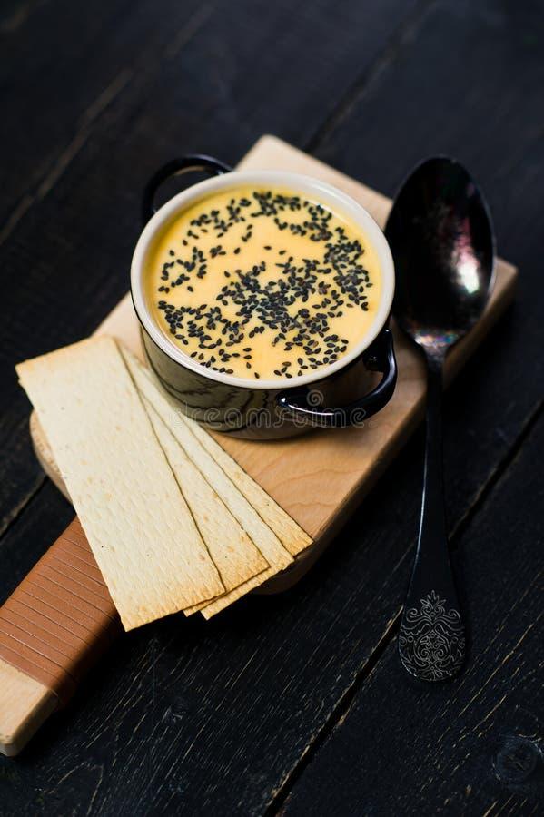 Σούπα κολοκύθας με το μαύρες σουσάμι και τις κροτίδες στοκ φωτογραφία