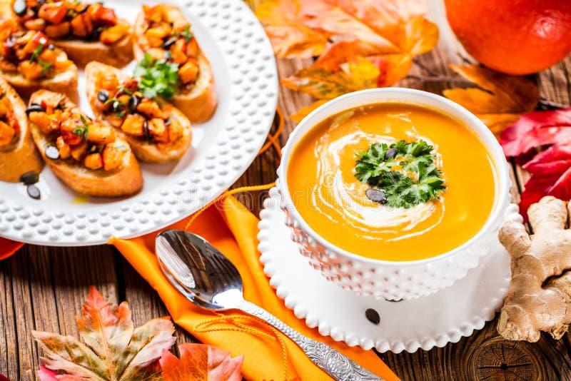 Σούπα κολοκύθας φθινοπώρου που εξυπηρετείται σε ένα άσπρο πιάτο με το brushetta κολοκύθας στοκ φωτογραφίες με δικαίωμα ελεύθερης χρήσης