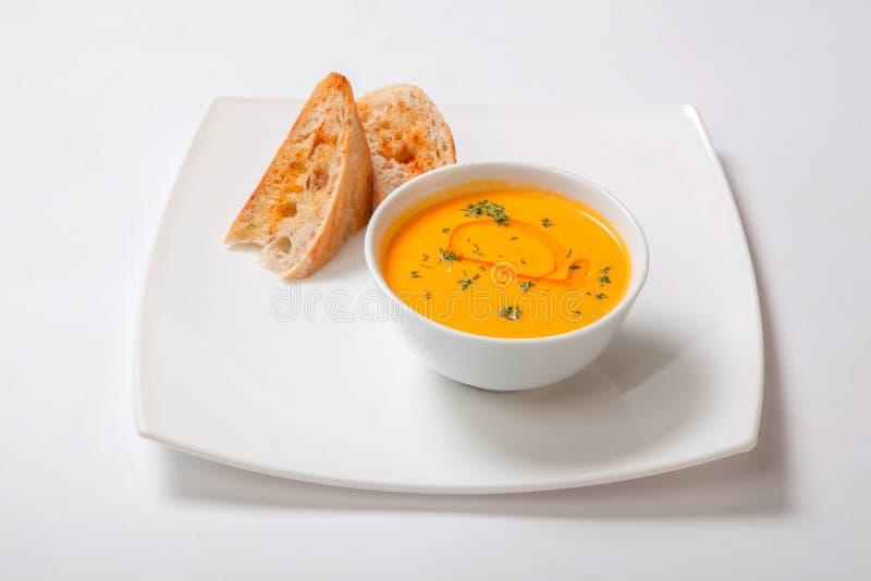 Σούπα κρέμας κολοκύθας στο άσπρο κύπελλο με τις φέτες του άσπρου ψωμιού στοκ εικόνα με δικαίωμα ελεύθερης χρήσης