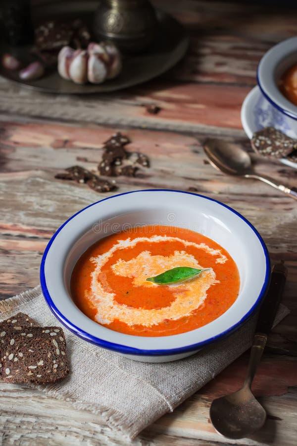 Σούπα κρέμας ντοματών με το βασιλικό στο άσπρο πιάτο στοκ φωτογραφία