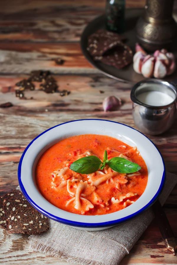 Σούπα κρέμας ντοματών με το βασιλικό στο άσπρο πιάτο στοκ εικόνες