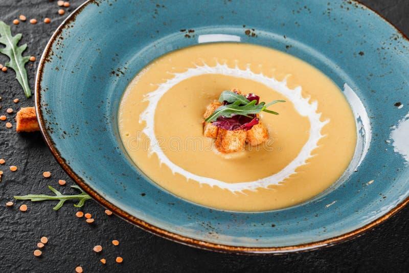 Σούπα κρέμας των φακών με τις τριμμένες φρυγανιές στο πιάτο στο σκοτεινό γκρίζο υπόβαθρο πετρών στοκ εικόνα
