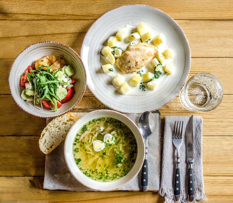 Σούπα με τα νουντλς και τα αυγά, κρέας με τον ανανά, φυτική σαλάτα, ένα ποτήρι του νερού και μαχαιροπήρουνα στοκ εικόνες