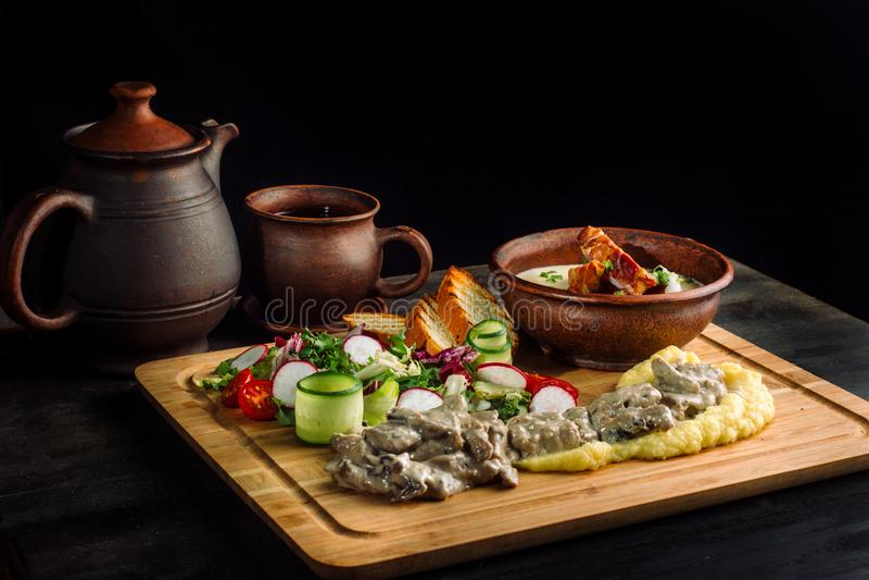 Σούπα μπιζελιών με το καπνισμένο κρέας σε ένα πιάτο αργίλου, goulash κρέατος με τα μανιτάρια και σάλτσα στοκ εικόνα με δικαίωμα ελεύθερης χρήσης