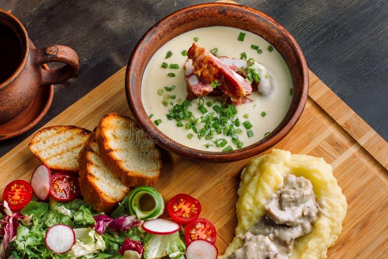 Σούπα μπιζελιών με το καπνισμένο κρέας σε ένα πιάτο αργίλου, goulash κρέατος με τα μανιτάρια και σάλτσα στοκ εικόνα