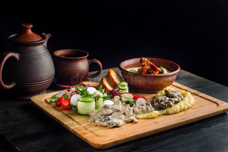 Σούπα μπιζελιών με το καπνισμένο κρέας σε ένα πιάτο αργίλου, goulash κρέατος με τα μανιτάρια και σάλτσα στοκ φωτογραφία με δικαίωμα ελεύθερης χρήσης