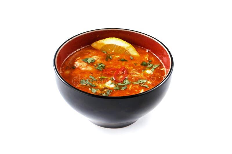 Σούπα ντοματών με το πιπέρι, το λεμόνι και τα χορτάρια σε ένα μαύρο και κόκκινο φλυτζάνι σε ένα απομονωμένο άσπρο υπόβαθρο στοκ φωτογραφία με δικαίωμα ελεύθερης χρήσης