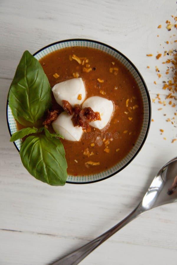 Σούπα ντοματών σε ένα κύπελλο με το μίνι τυρί μοτσαρελών, το φρέσκο πράσινο βασιλικό και τις ξηρές ντομάτες Τ στοκ φωτογραφίες με δικαίωμα ελεύθερης χρήσης