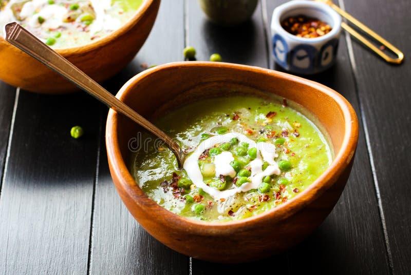 Σούπα πράσινων μπιζελιών που ολοκληρώνεται με τις νιφάδες ξινής κρέμας και κόκκινων πιπεριών στοκ φωτογραφία με δικαίωμα ελεύθερης χρήσης