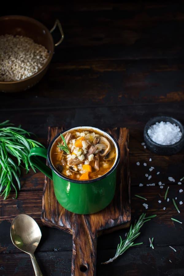 Σούπα στην εκλεκτής ποιότητας κούπα μετάλλων στο παλαιό ξύλινο υπόβαθρο στοκ εικόνες
