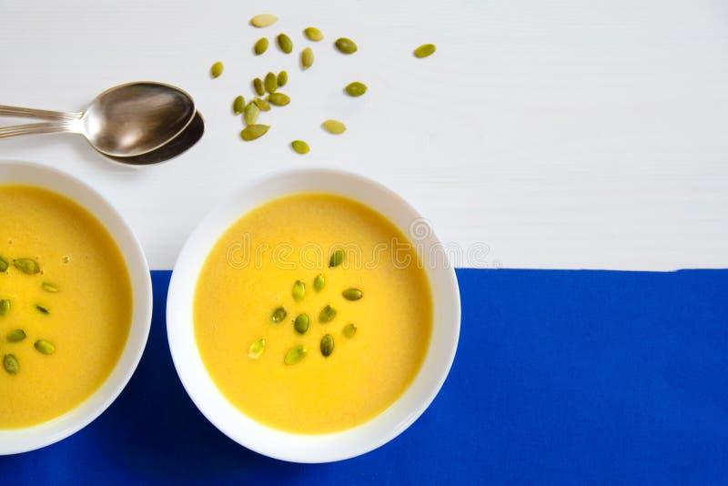 Σούπα των σπόρων κολοκύθας και ηλίανθων σε ένα άσπρο πιάτο με τα ασημένια κουτάλια σε ένα φωτεινό υπόβαθρο κατανάλωση έννοιας υγι στοκ φωτογραφίες με δικαίωμα ελεύθερης χρήσης