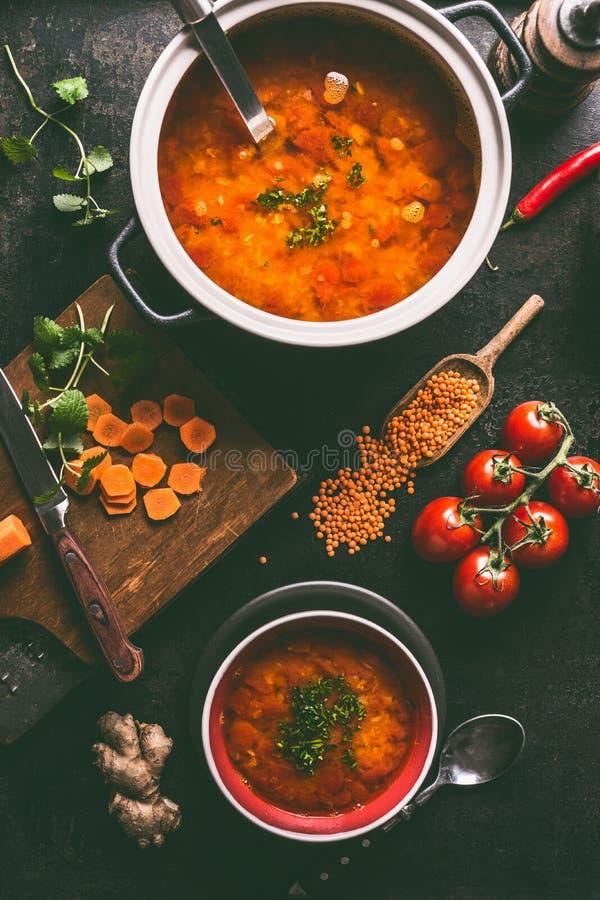 Σούπα φακών στο δοχείο και κύπελλο με το κουτάλι και την κουτάλα Μαγειρεύοντας συστατικά στο σκοτεινό αγροτικό επιτραπέζιο υπόβαθ στοκ εικόνες με δικαίωμα ελεύθερης χρήσης