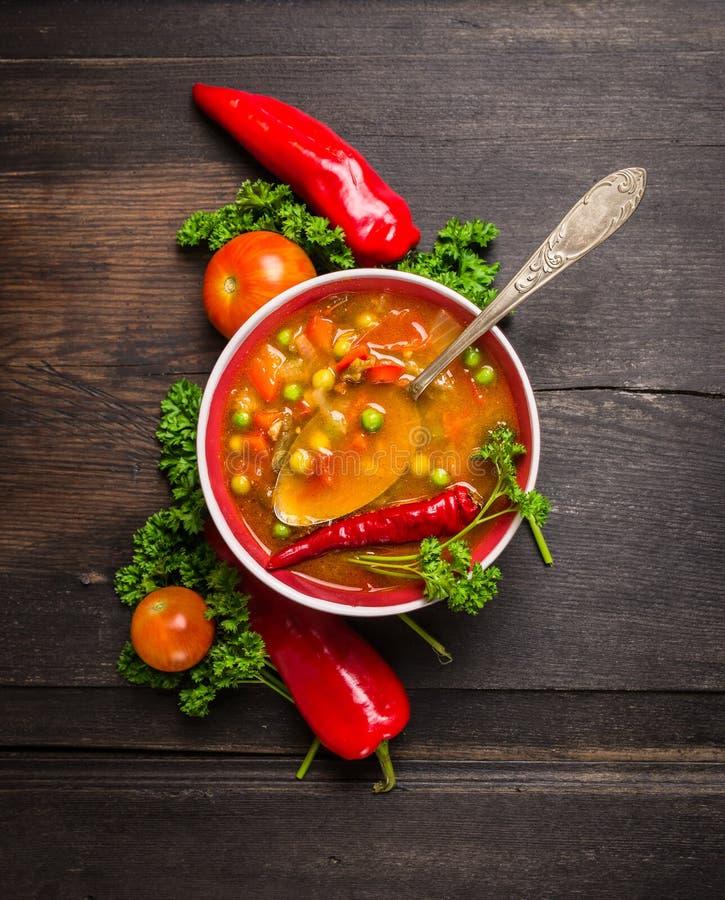 Σούπα Minestrone στο σκοτεινό ξύλινο πίνακα με το εκλεκτής ποιότητας κουτάλι και τα λαχανικά στοκ εικόνες