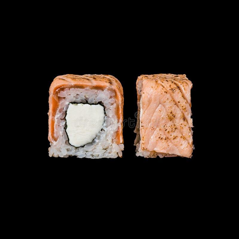 Σούσια Ο ρόλος με το τυρί σολομών και κρέμας, που απομονώθηκε στο μαύρο υπόβαθρο στοκ φωτογραφία