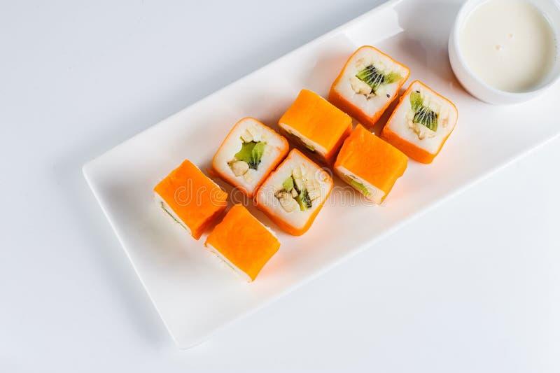 Σούσια της Maki επιδορπίων - ο ρόλος με τα διάφορα φρούτα στην πουτίγκα και την καρύδα ρυζιού ξεφλουδίζει στοκ εικόνα