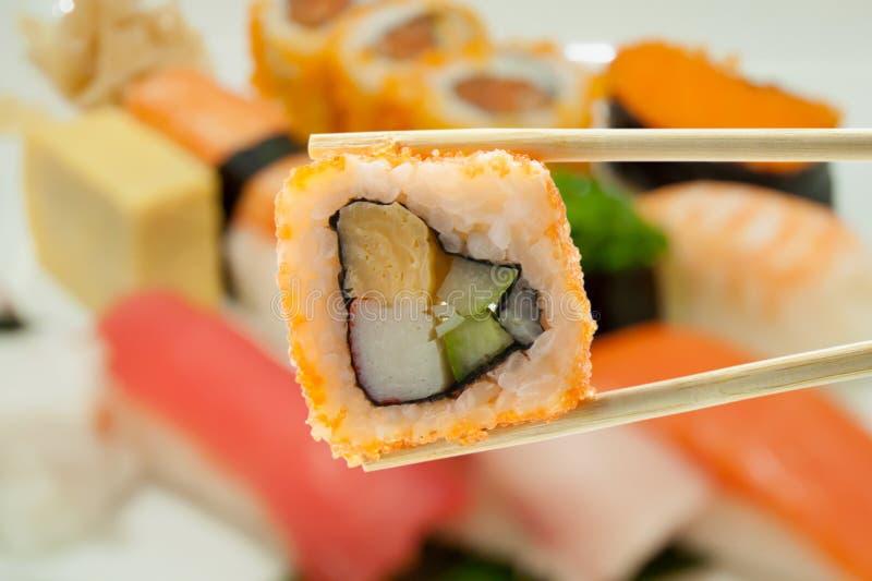 Σούσια chopsticks με τα σούσια θαμπάδων στοκ φωτογραφίες με δικαίωμα ελεύθερης χρήσης
