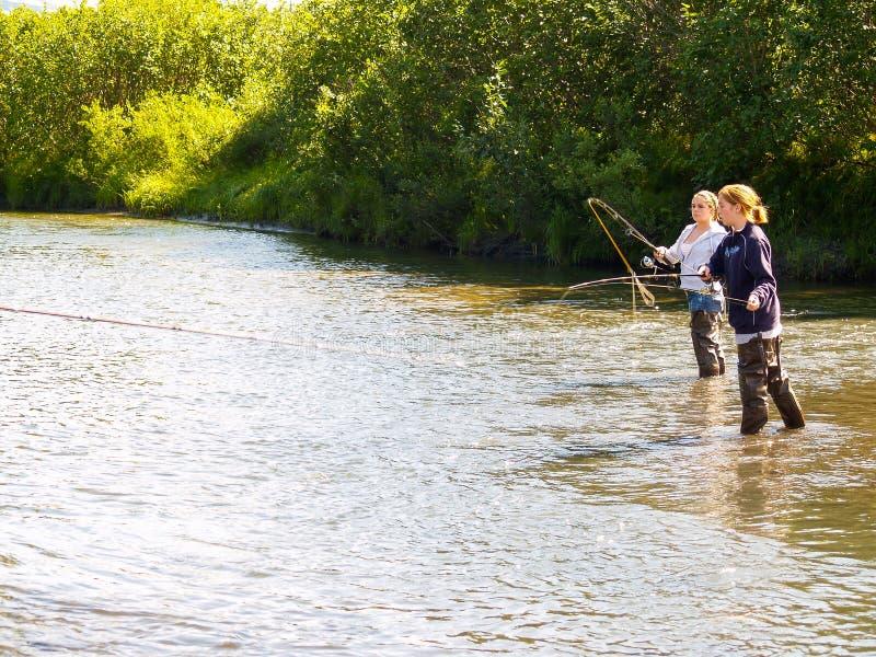 Σολομός δύο νέος γυναικών που αλιεύει στο μικρό ποταμό στην Αλάσκα στοκ εικόνες