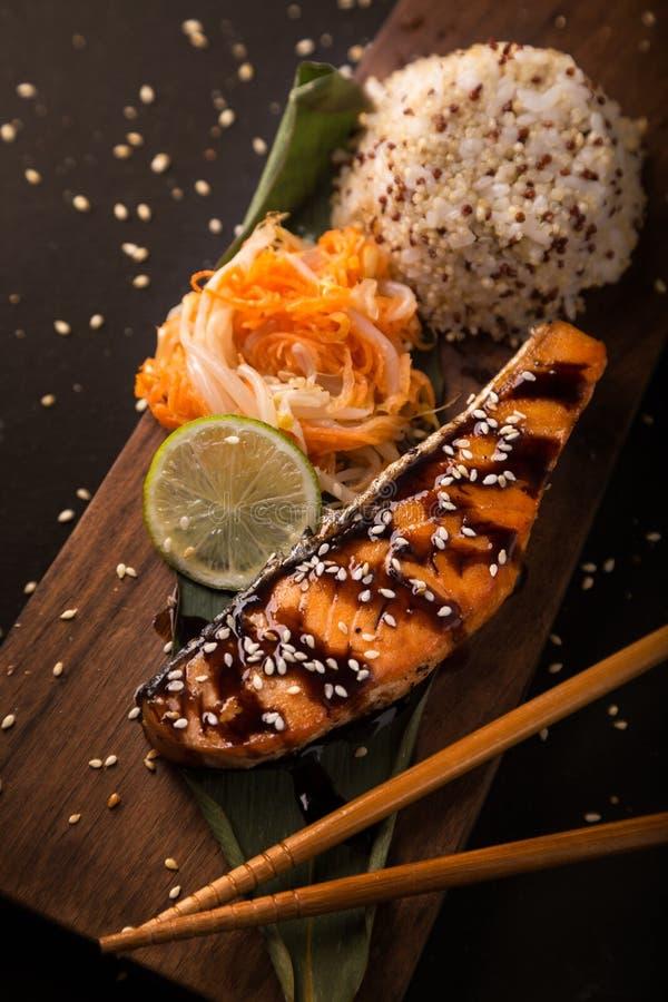 Σολομός Teriyaki με το ρύζι σε μια ξύλινη πιατέλα κορυφή στοκ φωτογραφία