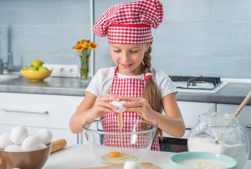 Σπάζοντας αυγά μικρών κοριτσιών στο κύπελλο στοκ φωτογραφία