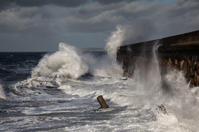 Σπάζοντας κύματα πέρα από τον κυματοθραύστη Holyhead στοκ εικόνες