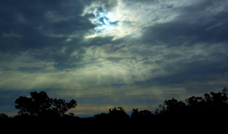 Σπάσιμο ήλιων μέσω των σύννεφων με τη σκιαγραφία των δέντρων στοκ φωτογραφία