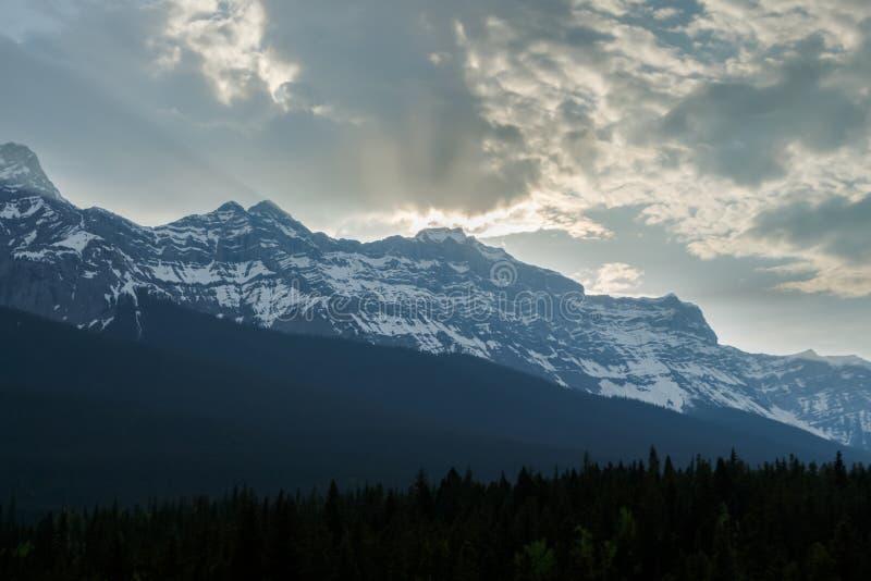 Σπάσιμο ήλιων μέσω των σύννεφων πέρα από τη σειρά βουνών στοκ εικόνες