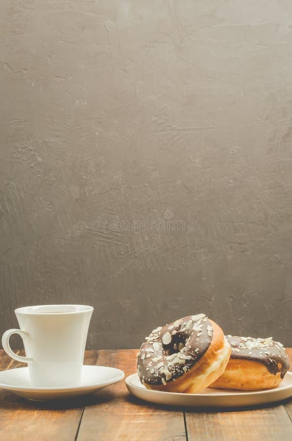 Σπάσιμο offee Ð ¡ Λευκό φλυτζάνι με το μαύρο καφέ και donat στο λούστρο σοκολάτας Σκοτεινό υπόβαθρο με το διάστημα αντιγράφων στοκ εικόνες με δικαίωμα ελεύθερης χρήσης