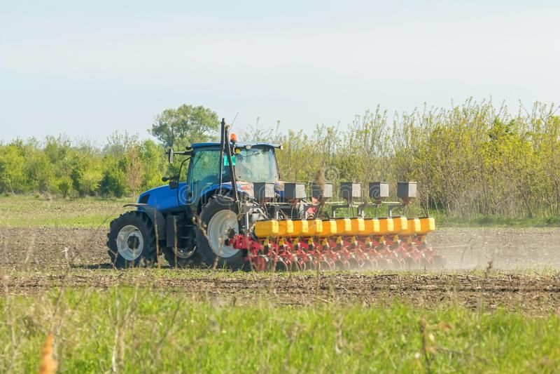 Σπέρνοντας συγκομιδές, γεωργικοί τομείς την άνοιξη, Farmer με τη σπορά τρακτέρ στοκ φωτογραφία με δικαίωμα ελεύθερης χρήσης
