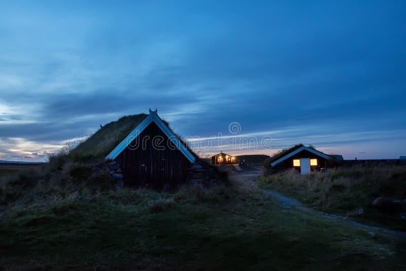 Σπίτια με μια χλόη-καλυμμένη στέγη στο σούρουπο στο λιβάδι το βράδυ o στοκ φωτογραφία
