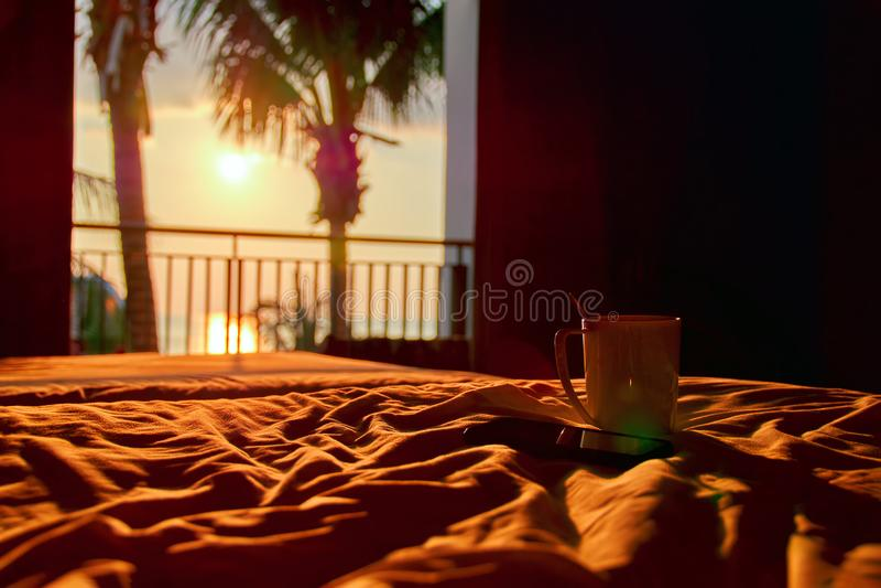 Σπίτι έννοιας άνετο στο ταξίδι Άσπρα κούπα και smartphone στο κρεβάτι στο ηλιόλουστο φως βραδιού από την ανοικτή πόρτα μπαλκονιών στοκ φωτογραφία