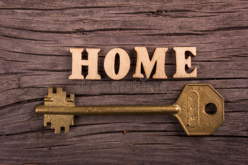 Σπίτι λέξης φιαγμένο από ξύλινες επιστολές με ένα κλειδί στοκ φωτογραφία