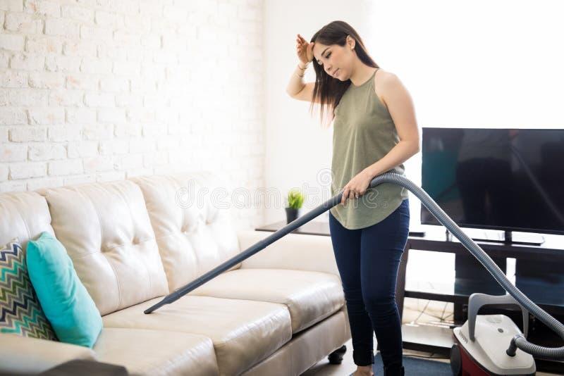 Σπίτι και καθαρότητα - καθαρίζοντας καναπές γυναικών στοκ εικόνα