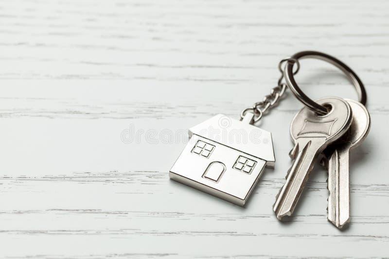 Σπίτι και κλειδιά Keychain στο άσπρο ξύλινο υπόβαθρο Διάστημα αντιγράφων για το κείμενο στοκ εικόνες
