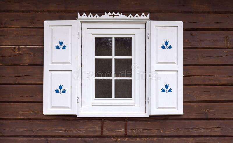 Σπίτι κούτσουρων με το διακοσμημένο παράθυρο στοκ φωτογραφίες με δικαίωμα ελεύθερης χρήσης