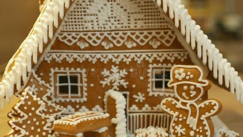 Σπίτι μελοψωμάτων και κέικ εξοχικών σπιτιών όμορφο, δέντρο με τα σπίτια και χιονάνθρωπος, που διακοσμείται με μια άσπρη τήξη βιομ στοκ φωτογραφίες
